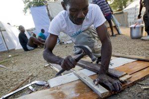 Haitian Builds Makeshift Shelter on Port-au-Prince Golf Course